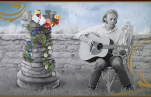 Stephen Stills sits next to a tower covered in flowers. In his lap is an acoustic guitar. This image is a screen grab from the Youtube Video